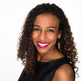 This is a profile picture of Victoria. She is a brown girl with curly hair and nice pink lipstick in this headshot.